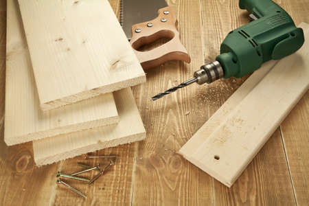 carpenter items: Wood work tools and planks. Including hand saw, drill,screws.