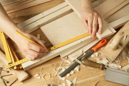 falegname: Workshop tavolo in legno con attrezzi. Le braccia dell'uomo di misura.