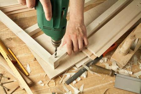 Houten workshop tafel met gereedschap. Man's armen boor plank.