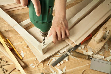 shavings: Wooden workshop table with tools. Mans arms drill plank. Stock Photo