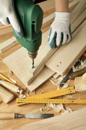 carpenter items: Wooden workshop table with tools. Mans arms drill plank. Stock Photo