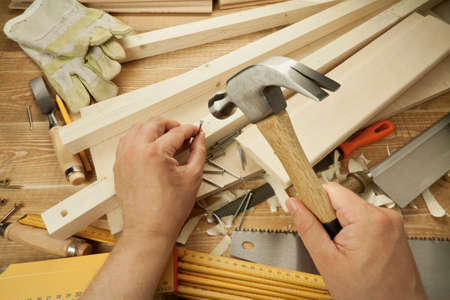 hammering: Wooden workshop table with tools. Mans arms hammering a nail Stock Photo