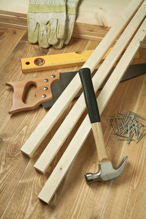 home repair: Hammer, saw, level, gloves, planks and nails on wooden floor