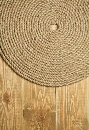 Twisted rope on wooden background photo