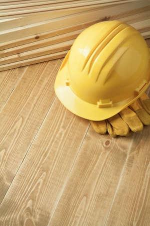 carpenter items: Construction background. Yellow helmet on wooden floor.