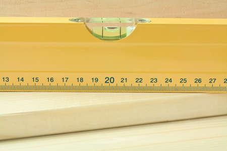 Yellow level tool on wood plank. photo