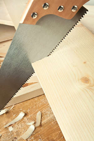 Wood workshop. Hand saw cutting plank. Stock Photo - 9904417