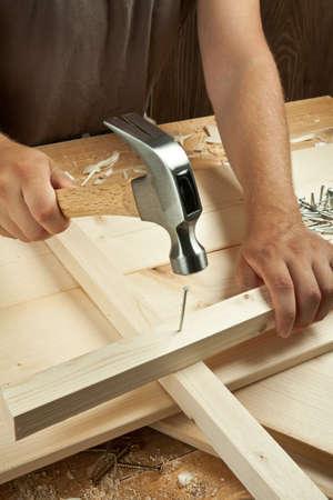 Wood workshop. Carpenter hammering a nail. photo