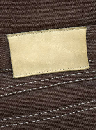 Blank leather label sewed on pants. photo