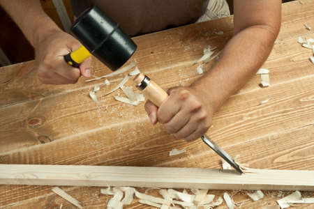 carpentry tools: Wood workshop. Carpenter working with chisel. Stock Photo