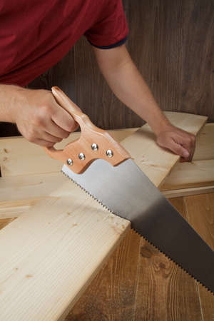 Hout workshop. Timmerman snijden plank met hand zag. Stockfoto