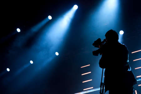video camera: Cameraman silhouette on a concert stage Stock Photo