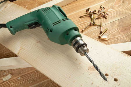electric drill: Electric drill on wooden board Stock Photo