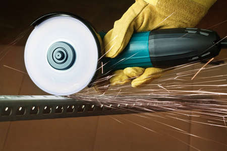 Worker sawing metal with electrical saw. photo