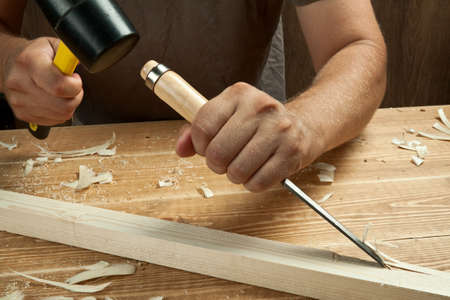 shavings: Wood workshop. Carpenter working with chisel. Stock Photo
