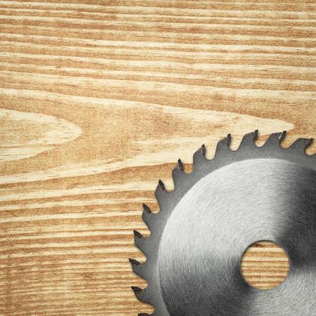 Circular saw blade on a wood board. photo