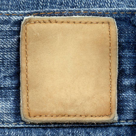 Blank leather jeans label sewed on a blue jeans. Can be used as background for your text. photo