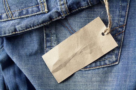 denim wear: Jeans trousers with blank paper label Stock Photo