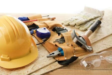 alicates: Casco amarillo y cinturón de herramientas.
