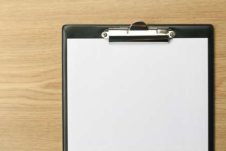 Clipboard with blank paper on office table