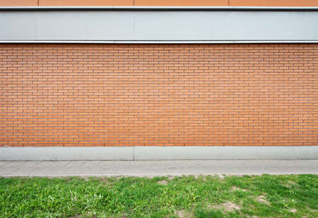 Empty brick wall and green grass ground. photo