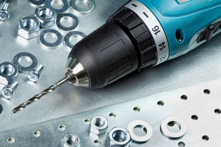screw key: Metal workshop  Cordless electric drill  Stock Photo