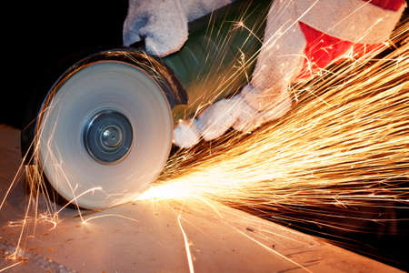 Worker cutting metal with grinder  Stock Photo
