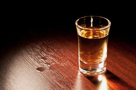Whiskey shot in a dark bar   Stock Photo - 17095616