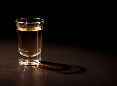 Whiskey shot in a dark bar   photo