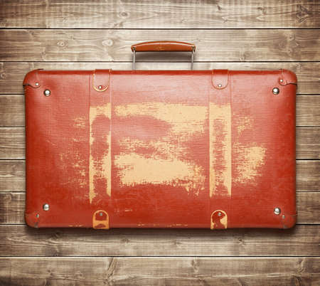 Vintage red suitcase isolated on wooden background photo