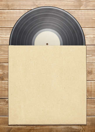 Old vinyl record in a paper case, on wooden table.