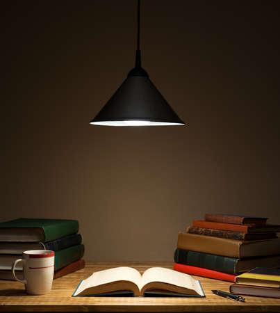 Boeken op houten tafel onder lamp licht Stockfoto