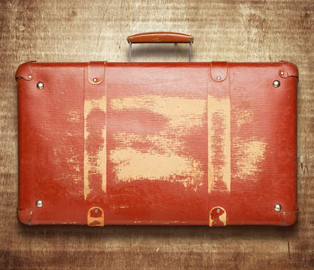 leather briefcase: Vintage red suitcase on wooden background