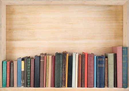 columna vertebral: Libros viejos en un estante de madera. Foto de archivo