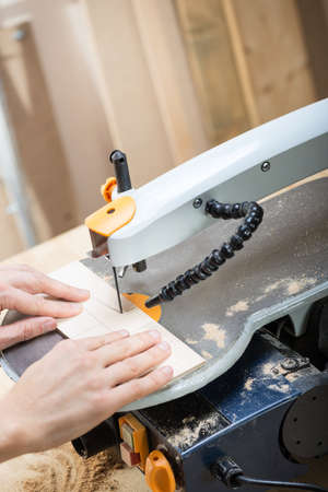 saws: Cutting plywood board by using electrical jigsaw. Stock Photo