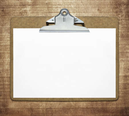 Clipboard with blank sheet of paper on wooden table