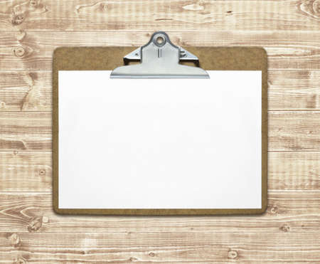 Clipboard with blank sheet of paper on wooden table photo