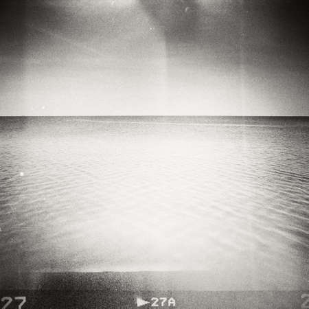 old film: Sunny day on the beach. Grainy film effect.