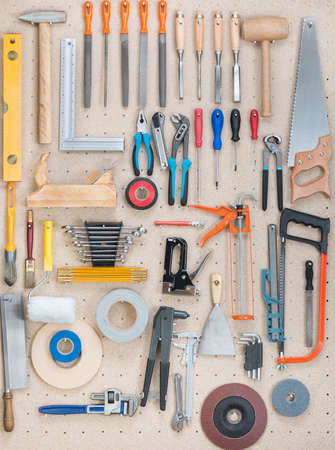Various carpentry, construction tools hanging on the board. photo