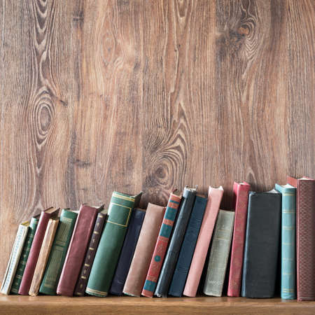 book spine: Old books on wooden shelf. Stock Photo