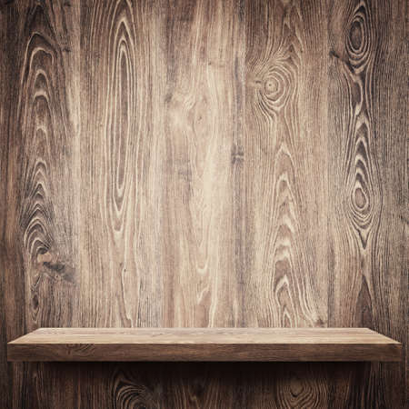 Empty shelf on wooden wall photo
