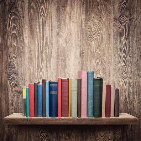 bookshelves: Old books on a wooden shelf.