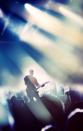 concierto de rock: Roca escenario para conciertos. Guitarrista que juega en la guitarra eléctrica.