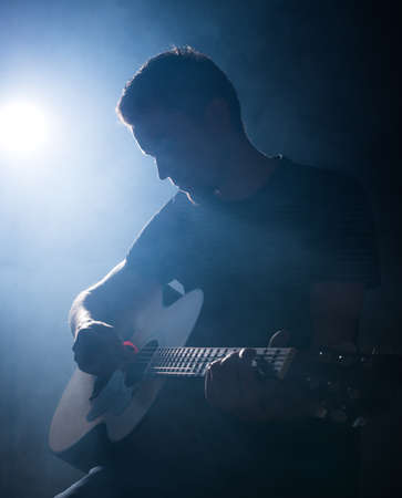 jazz singer: Guitarist playing acoustic guitar. Unplugged performance in the dark. Stock Photo