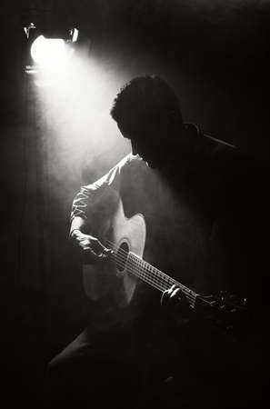 ギタリスト アコースティック ギターを弾く。暗闇の中でアンプラグドのパフォーマンス。 写真素材