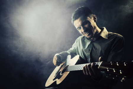 Guitarist playing acoustic guitar. Unplugged performance in the dark. Archivio Fotografico