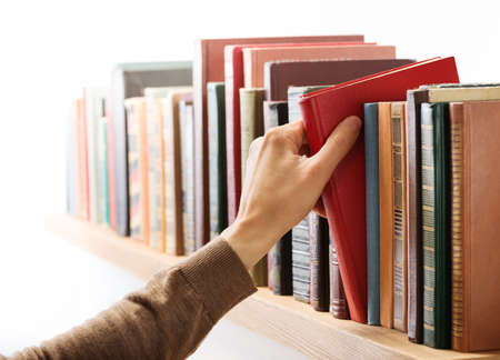 OLD LIBRARY: Hand taking book from the shelf.