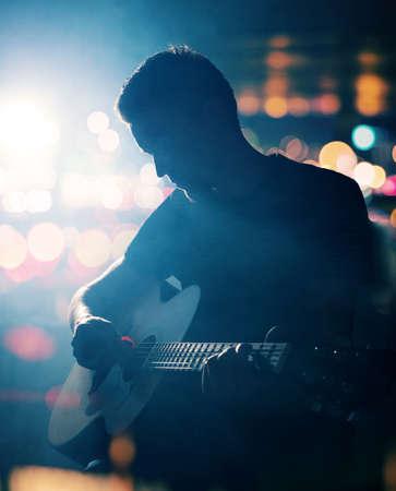 gitara: Gitarzysta gra na gitarze akustycznej. Unplugged wydajność w ciemności. Zdjęcie Seryjne