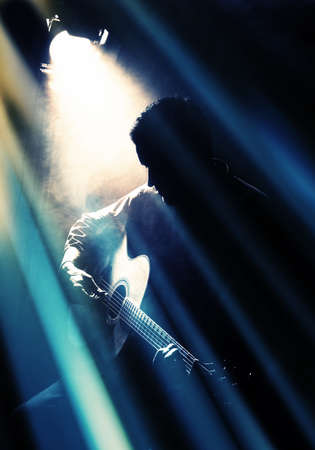 player: Guitarist playing acoustic guitar. Unplugged performance in the dark. Stock Photo