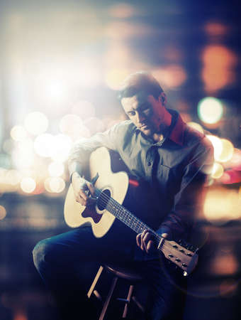 the musician: Guitarist playing acoustic guitar. Unplugged performance in the dark. Stock Photo